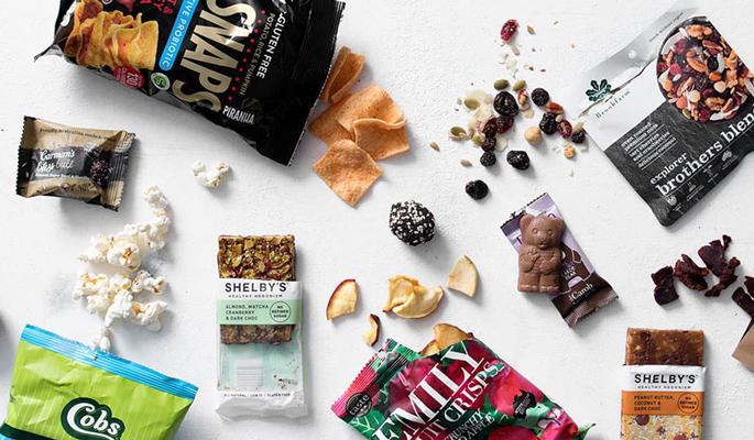 Mindeféle snackek szétszórva egy fehér asztalon: chipsek, aszalt gyümölcsök, csokoládé, kókuszgolyó.