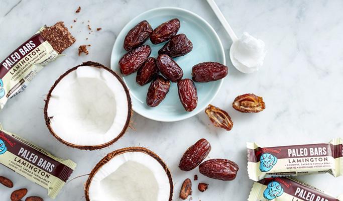 Fehér asztalon gyümölcs szeletek és azok alapanyagai: datolya, kókuszdió és vanília rudak.