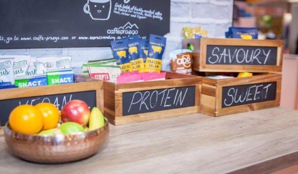 Egészséges snackek és gyümölcsök tárolókban egy irodai konyhapulton.
